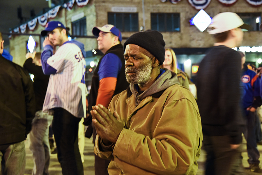 Chicago Cubs fan Wayne Tucker prays outside of Wrigley Field during the World Series.