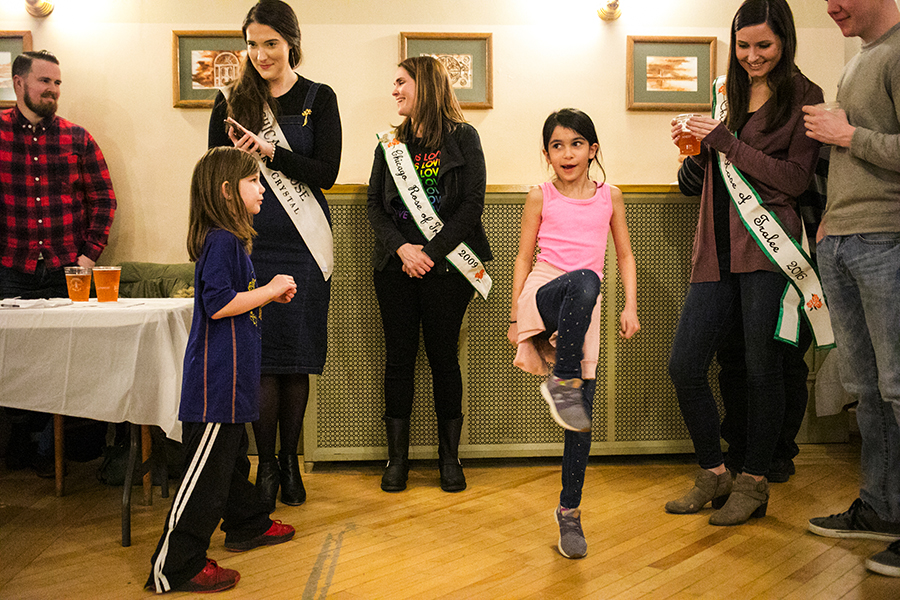 Aine McNulty dances to Irish music next to her mother, Deirdre (to her left), while the O'Hara School of Irish Dancers performs around the corner at the Irish American Heritage Center's Annual Lenten Fish Fry.