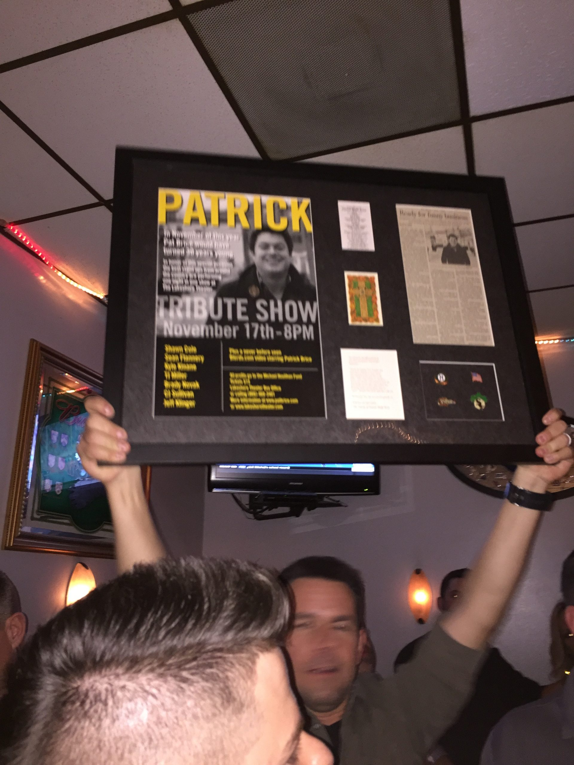 """Gerry Amelio, a longtime friend of the late Pat Brice, proudly holds up the """"Traveling Pat""""—a mobile shrine gifted to someone new each year—before passing it to Rich Considine."""