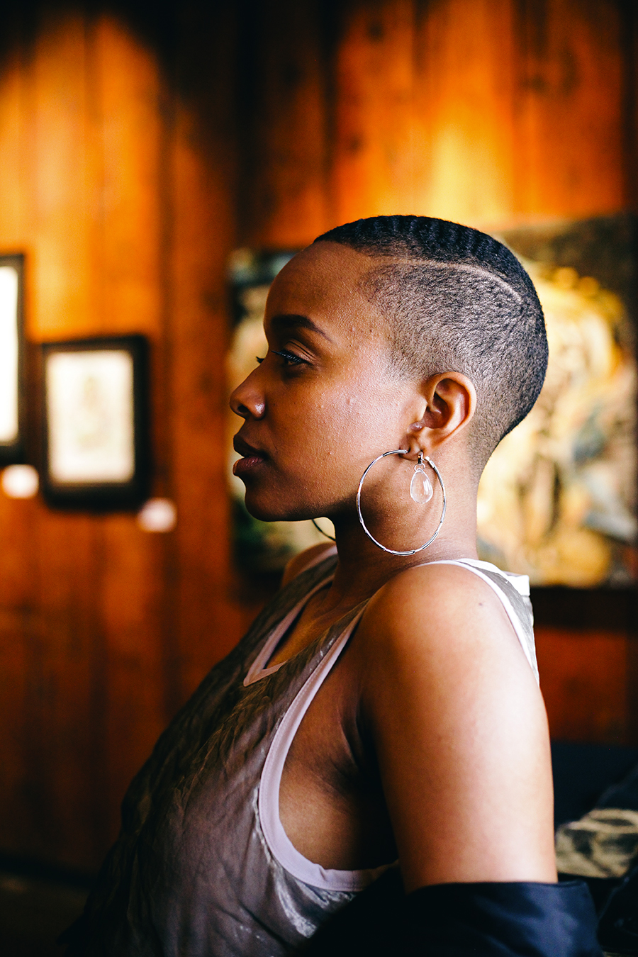 """Jamila Woods in the Dr. Margaret Burroughs Gallery, named after the SSCAC cofounder who also helped open the DuSable Museum of African American History in 1961. The gallery currently hosts the group exhibit """"Flowers in the Garden: A Tribute to the Struggles and Triumphs of the Black Woman."""""""