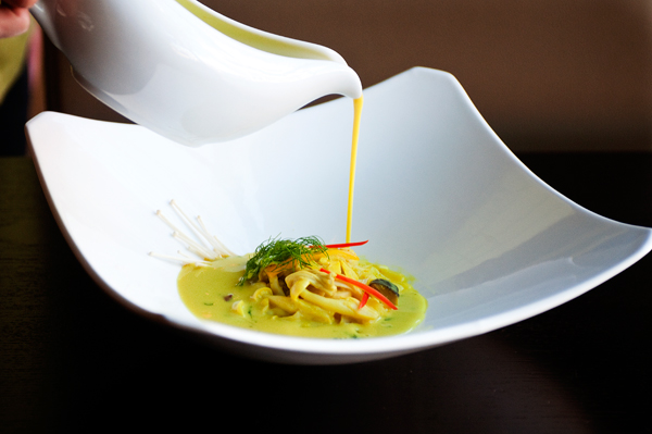A server pours turmeric-infused curry over king, oyster, and enoki mushrooms; hearts of palm; and sunchokes.
