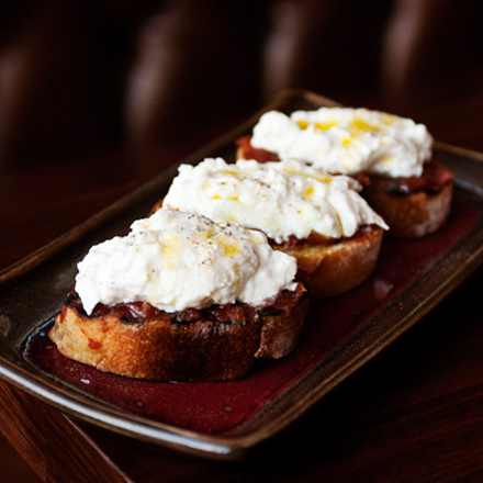 A salty olive oil-drizzled pillow of creamy burrata atop a thick smear of salty-sweet tomato marmalade.
