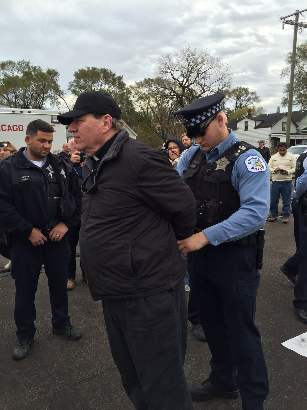 Police arrest Rev. Jim Galuhn of the East Side United Methodist Church.