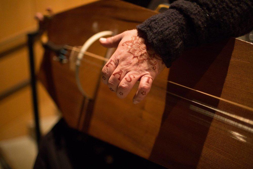 Zerang's hand on the Coffin's strings
