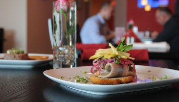 Garlic toast mounted with thick coils of pickled herring, pickled onions, and julienned apples