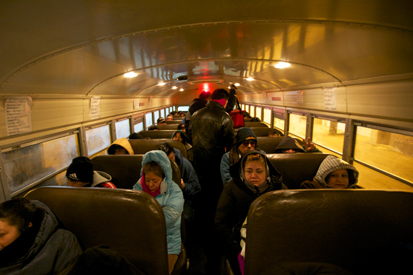 """In the early morning hours of January 18, workers board a yellow school bus owned by the raitero Rigoberto """"Rigo"""" Aguilar."""