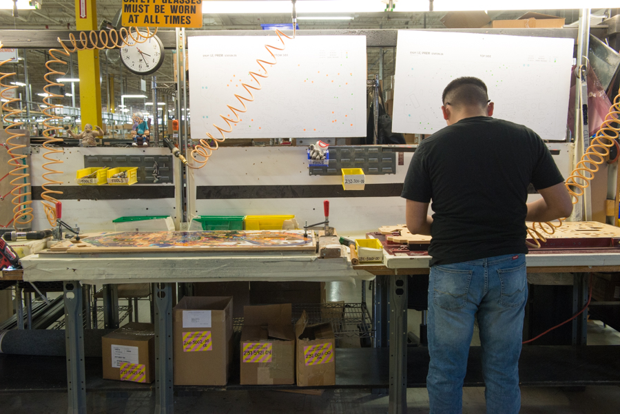 A worker finishes the a pinball playfield before it's placed in a cabinet