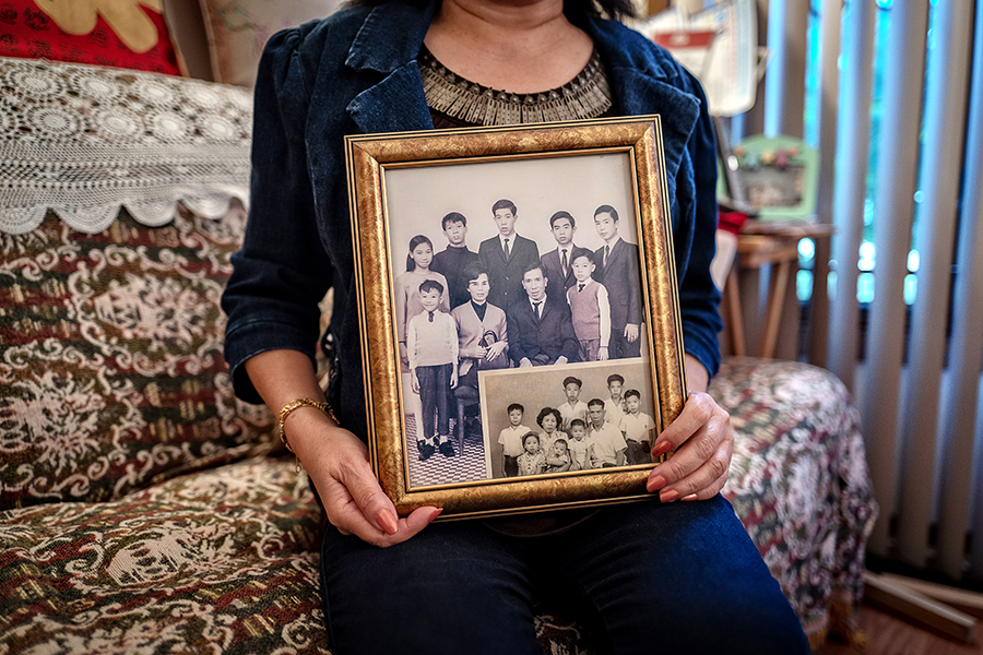 """She proudly holds a photo of her family back in Hong Kong. """"They were very expensive,"""" she says of the studio portraits. """"But my mother made sure we got them done."""""""