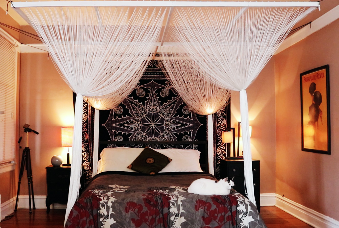 Master bedroom with a canopy of white string over the bed