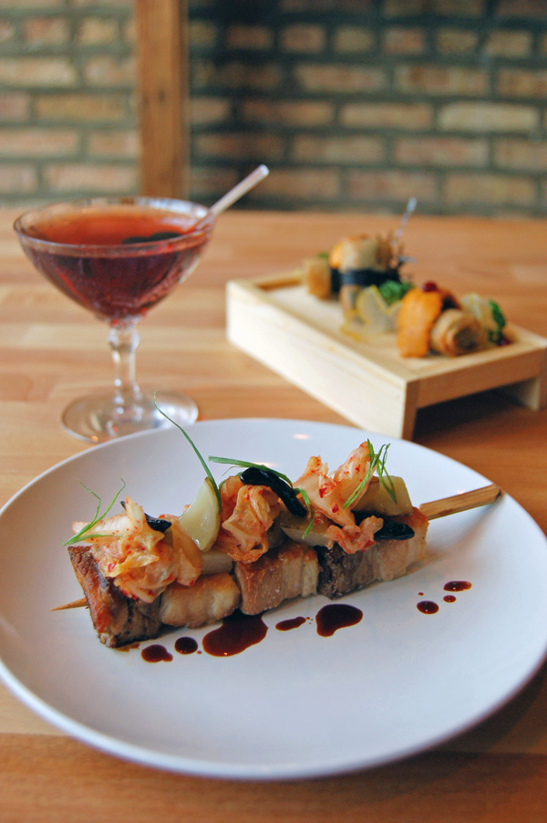 Pork belly skewer (foreground); crispy fried uni-stuffed egg rolls (background); and Three Arrows cocktail