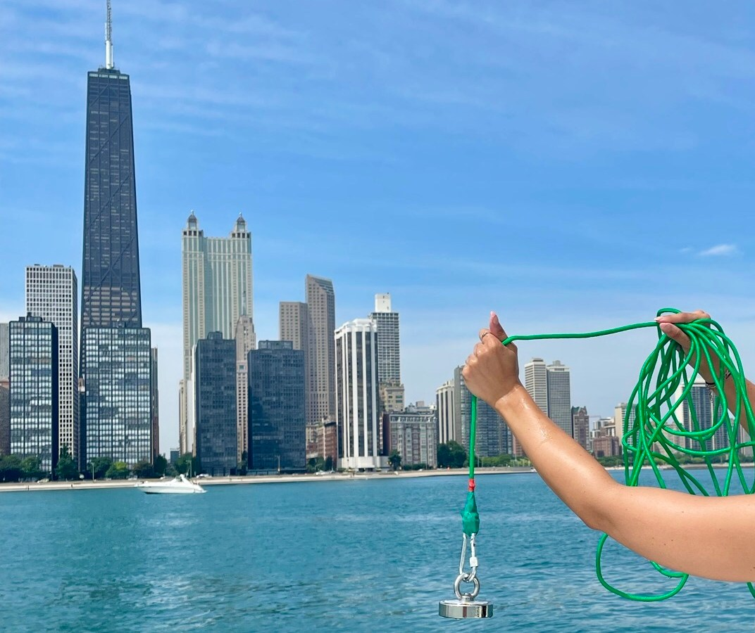 A hand holding a magnet on a rope in the foreground with the Chicago skyline in the background.