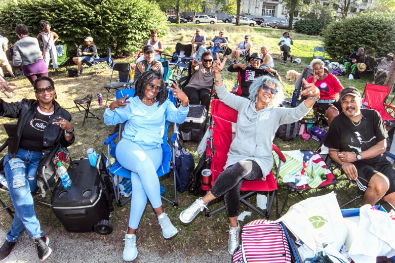 A group of friends in camping and patio chairs on the lawn at the Hyde Park Jazz Festival