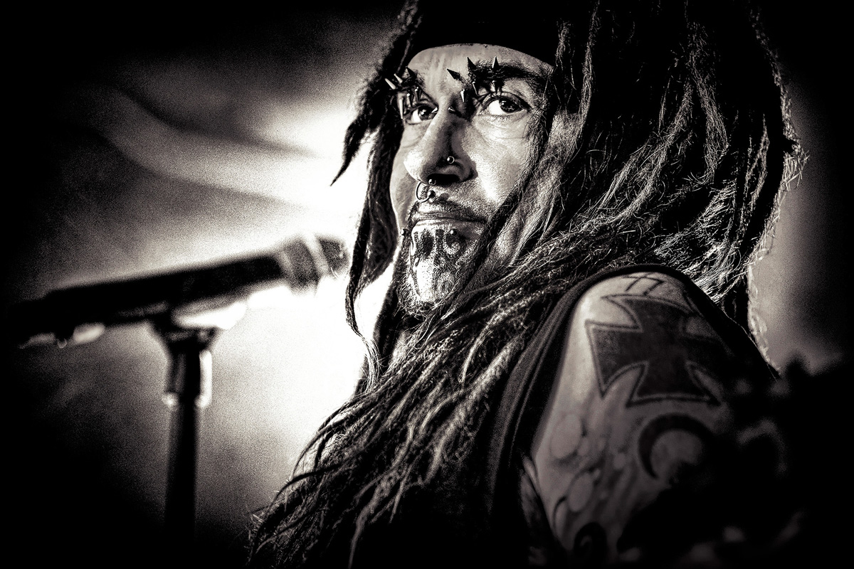 Black and white image of Ministry's Al Jourgensen standing at a microphone against a halo of light