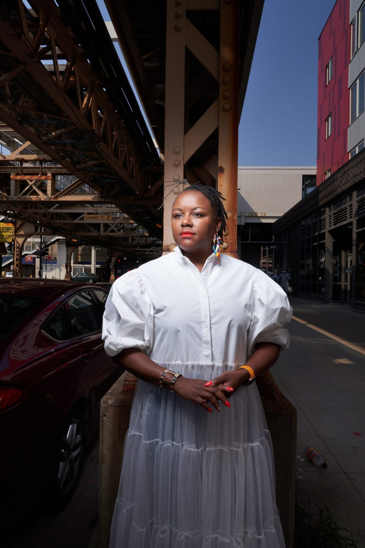Woman in white dress underneath elevated train tracks