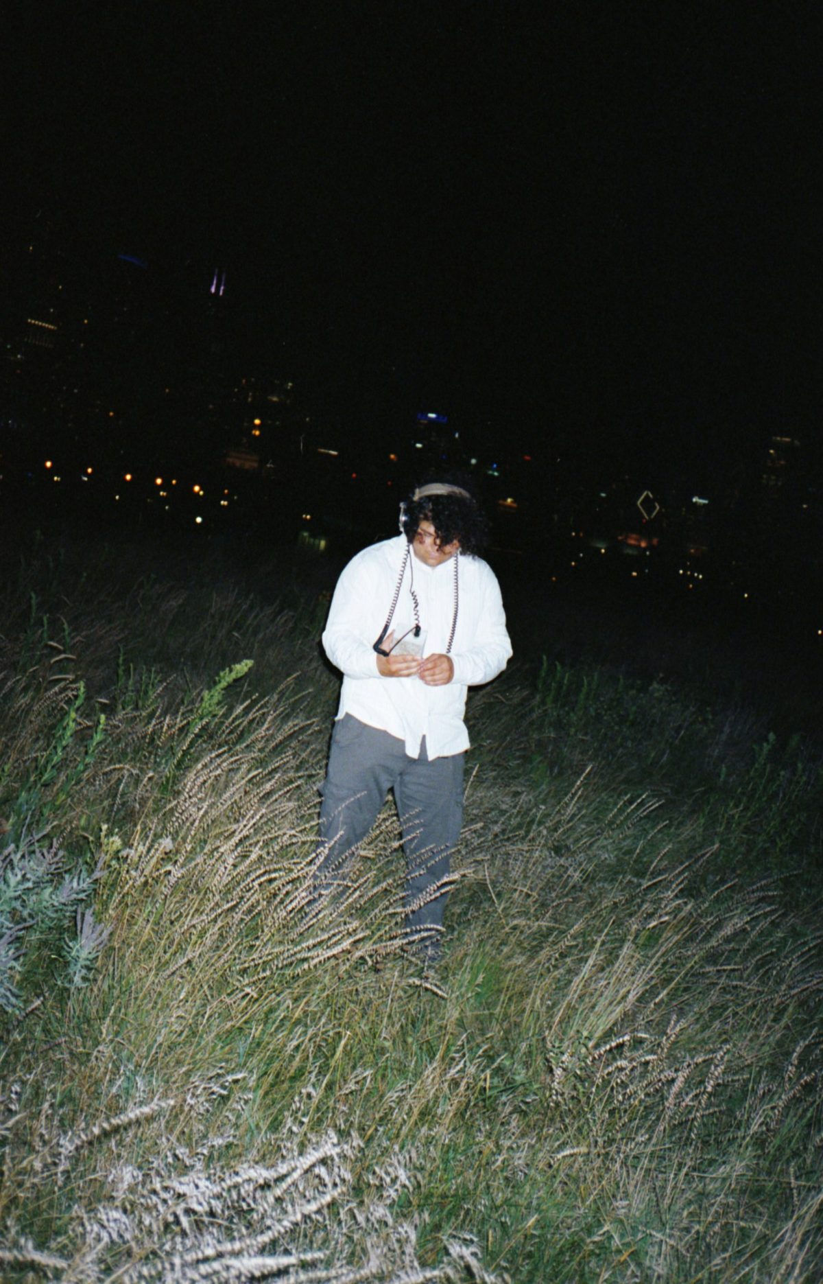 Man wearing headphones standing in field at night