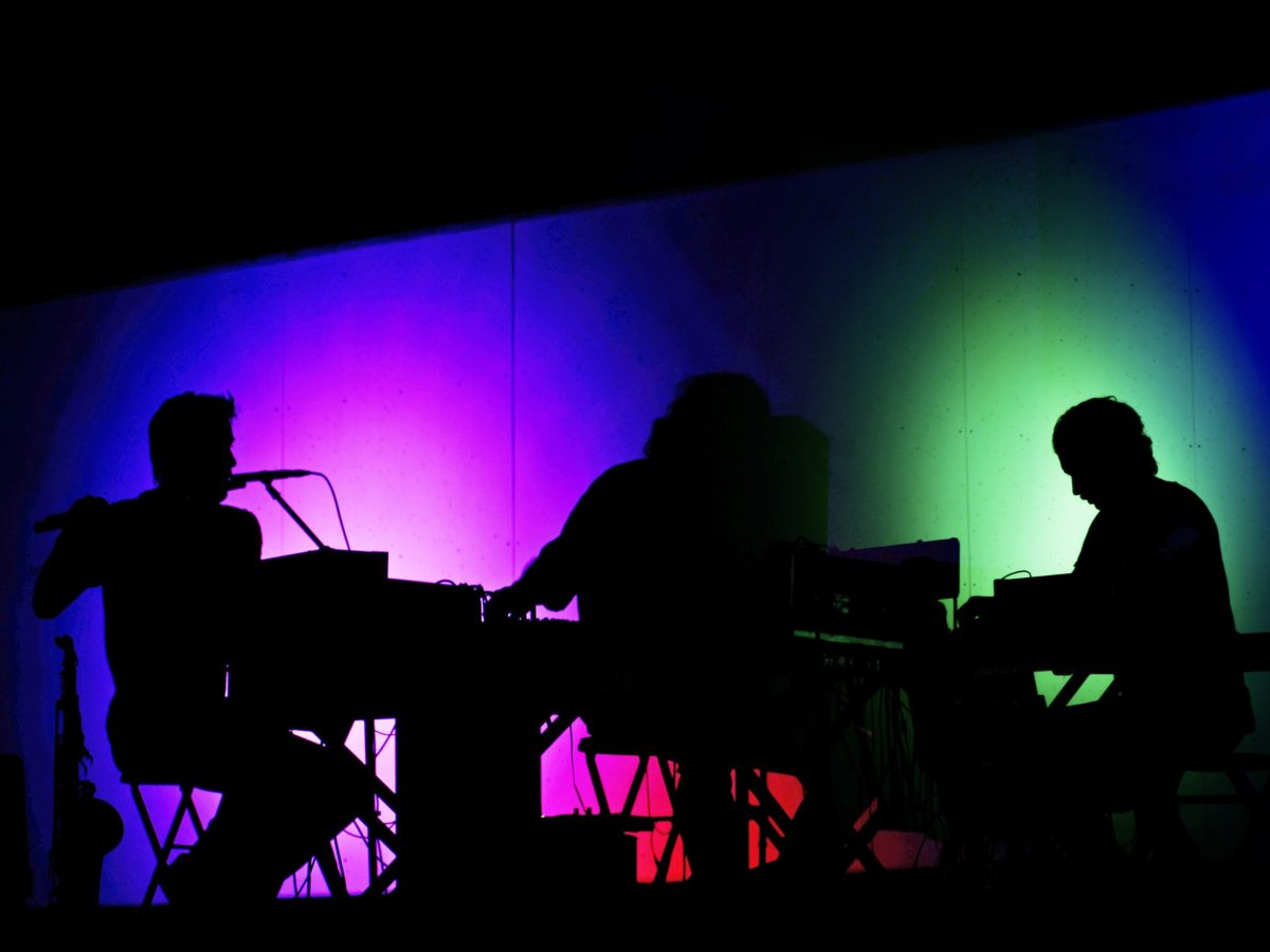 Rob Frye, Cooper Crain, and Daniel Quinlivan of Bitchin Bajas perform in darkness, silhouetted against colored lights.
