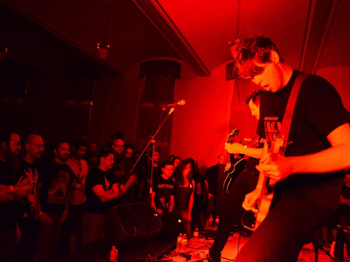 Guitarist of Kowloon Walled City bathed in red light while performing