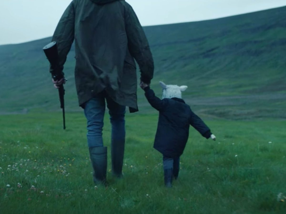 An adult with a gun holds hands with a child with a lamb's head as they walk
