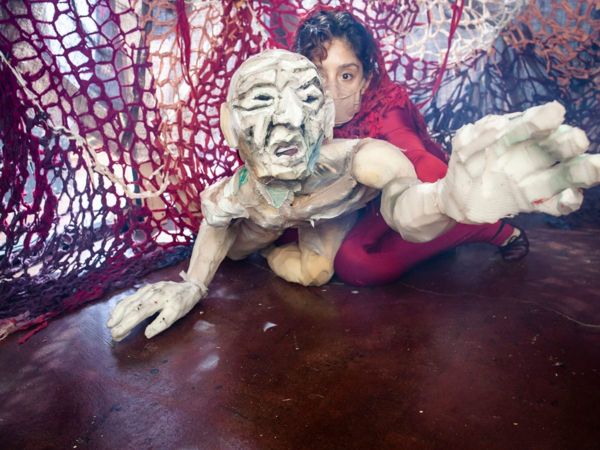 White humanlike puppet lying on the floor, operated by a woman in red laying next to puppet.