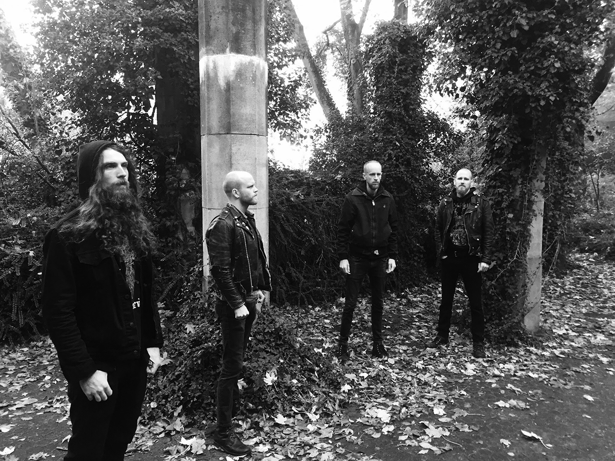 the band Yellow Eyes standing outside in front of some trees with fallen leaves on the ground, each band member is wearing a black jacket