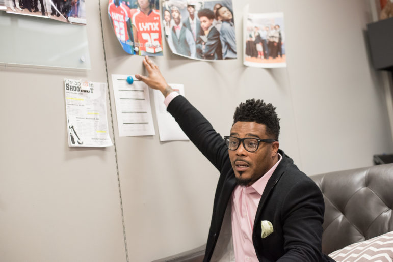 """Principal Christopher Goins points to a photo of two Butler students who died in separate shootings last school year. It was the first time he'd ever lost students to gun violence and he struggled to help students and teachers cope with the losses. """"I just asked for God to guide me. And I had to just go with my intuitions and what I felt people needed."""""""