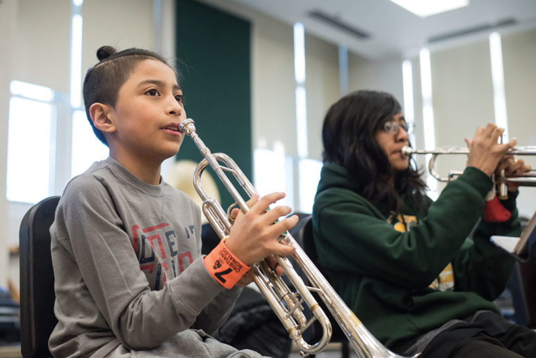 On Saturdays, Kelly High School music instructors and students conduct free music clinics for elementary students, such as Saucedo Scholastic Academy student Alex Farjado (left). The clinic is one of many ways Kelly reaches out to elementary schools.