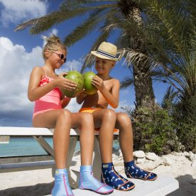2 kids say cheers with coconuts