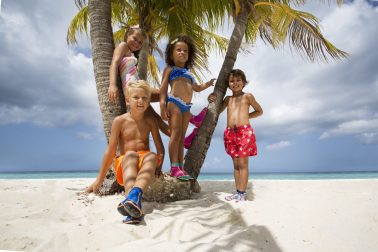 Kids posing their Duukies Beachsocks under palmtree