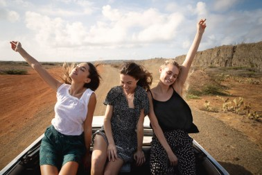 Models in car on desert area in Curacao