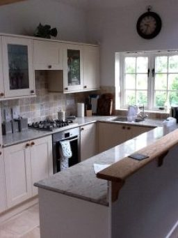 Kitchen area showing pale painted units with round, dark wooden handles, hob and oven and lovely view through white-painted casement windows with large clock on the wall above.
