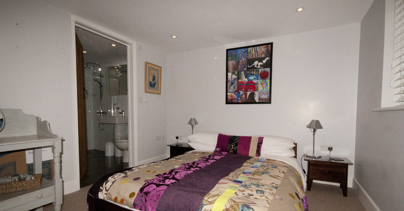Bedroom 1, with white-painted walls, a double bed with colourful duvet, and showing the ensuite bathroom in the background