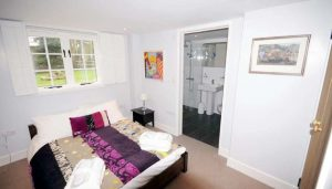 Bedroom 2 with double bed, white-painted casement window and ensuite.
