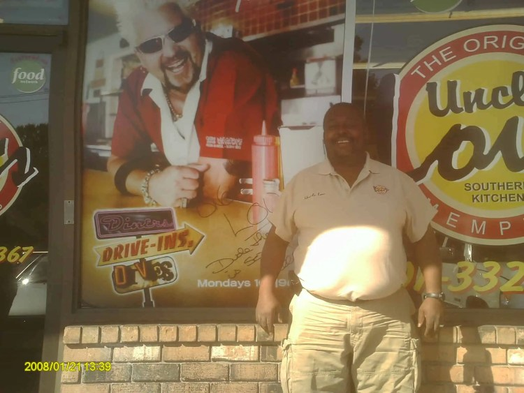 Uncle Lou outside of his store in front of Guy Fieri poster with clip on cell phone belt (lol)