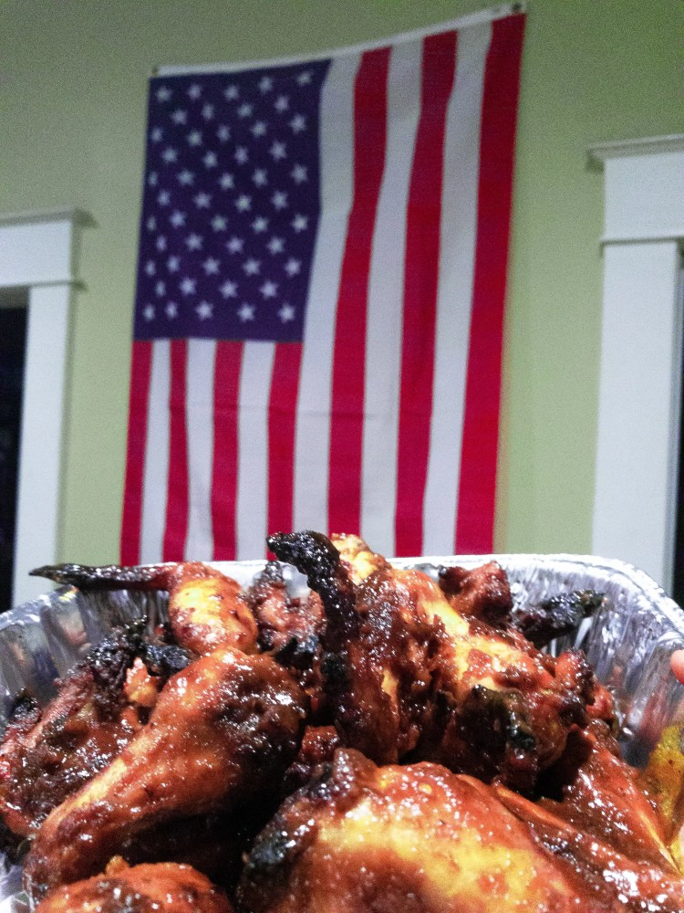 A batch of fried chicken wings in front of an american flag