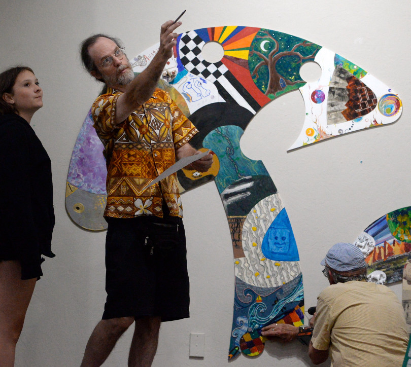 """Artists Olive Sisk, Titus Woods and David Sisk, AKA """" Sisko""""  left to right work to assemble a """"Puzzle Show"""" at the Chico Art Center in Chico Calif. Friday June 8, 2018. The piece is made from over 320 puzzle pieces by many artists. (Bill Husa -- Enterprise-Record)"""