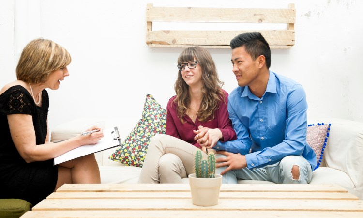Couple on a couch talking with a therapist