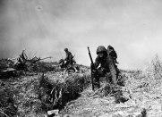 """Marines movendo-se com o que foi posteriormente intitulada """"Vale da Morte"""" por causa de mais de 125 mortes em 8 horas durante a travessia. Um homem com uma BAR cansado durante a travessia pelo vale da morte. Okinawa – 1945"""