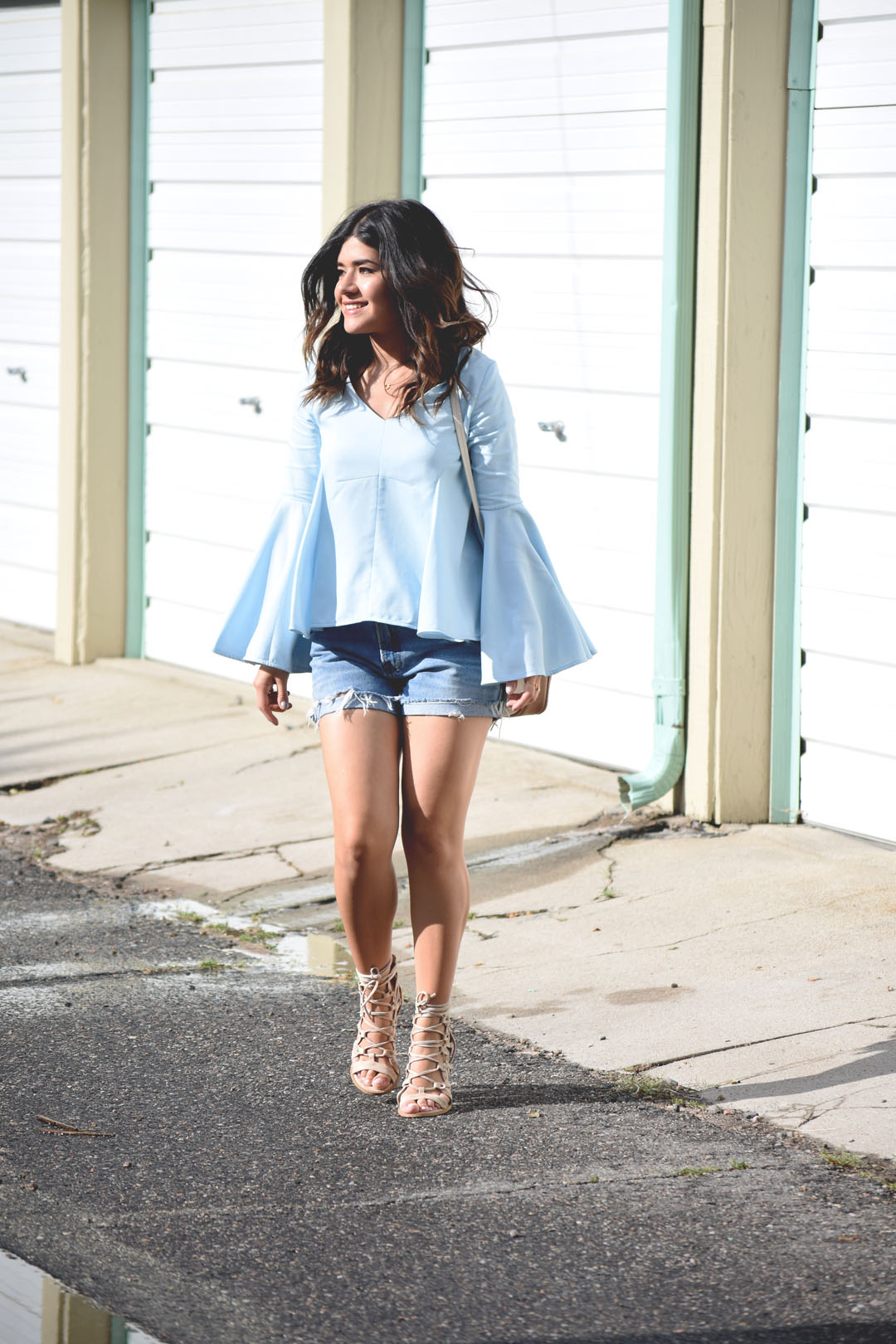 Carolina Hellal of the fashion blog Chic Talk wearing a Chicwish serene top with bell sleeves, vintage denim shorts and Lasula lace up sandals