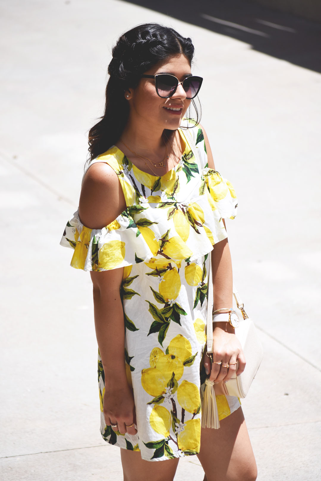 Carolina Hellal of Chic Talk wearing a Romwe summer lemon printed dress, Nordstrom sunglasses, and H&M beige crossbody bag with tassels.