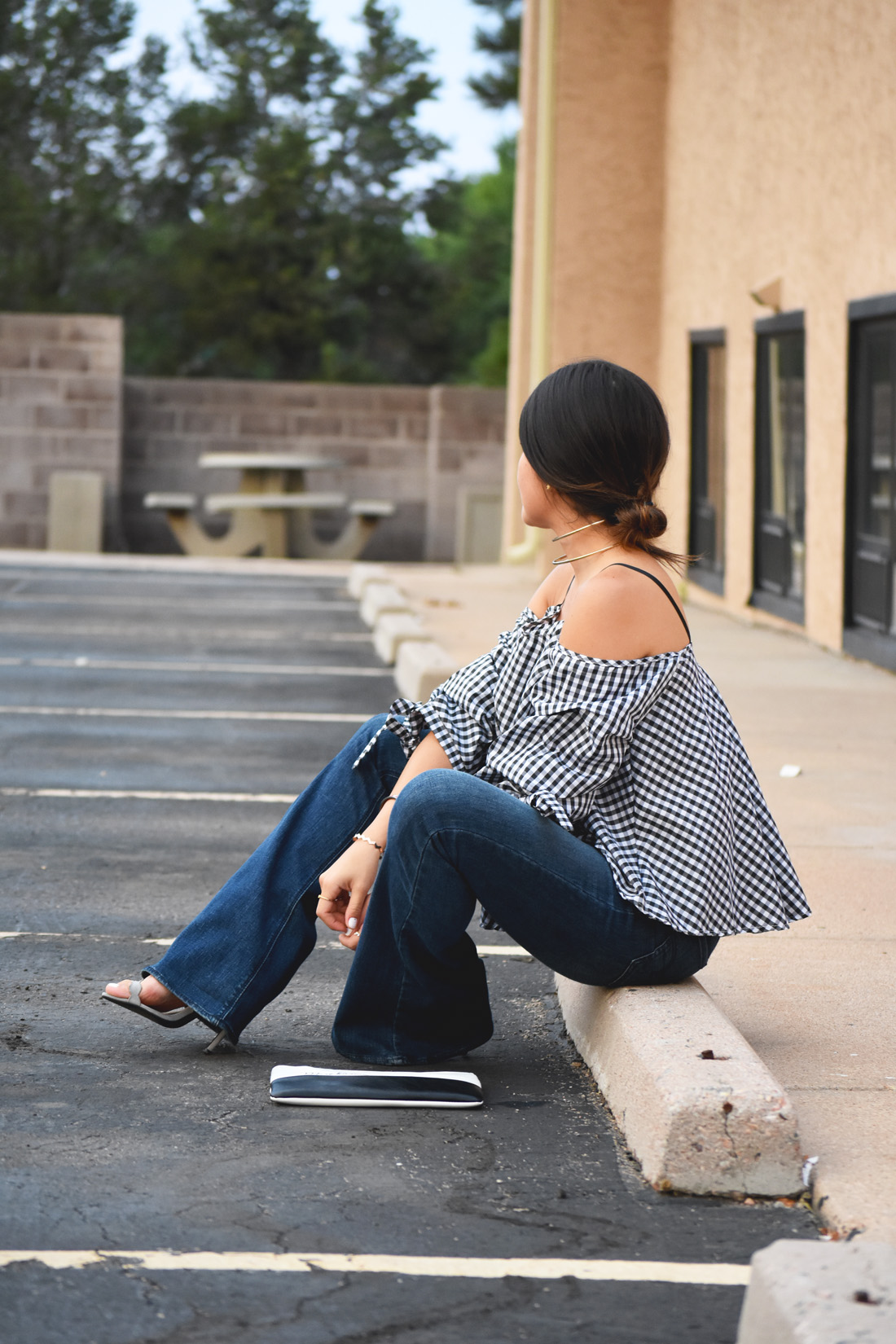 Carolina Hellal of Chic Talk wearing a chicwish gingham off the shoulder top, American Eagle bell bottom jeans, and le motto black and white clutch