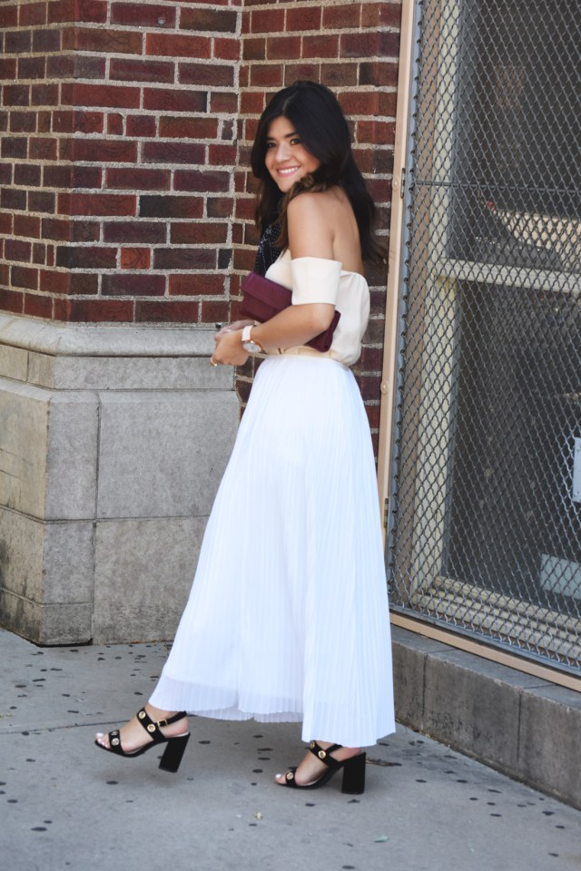 Carolina Hellal of Chic Talk wearing a Kensie Pleated white skirt, shein beige top, public desire black suede sandals, and pretty fast burgundy clutch