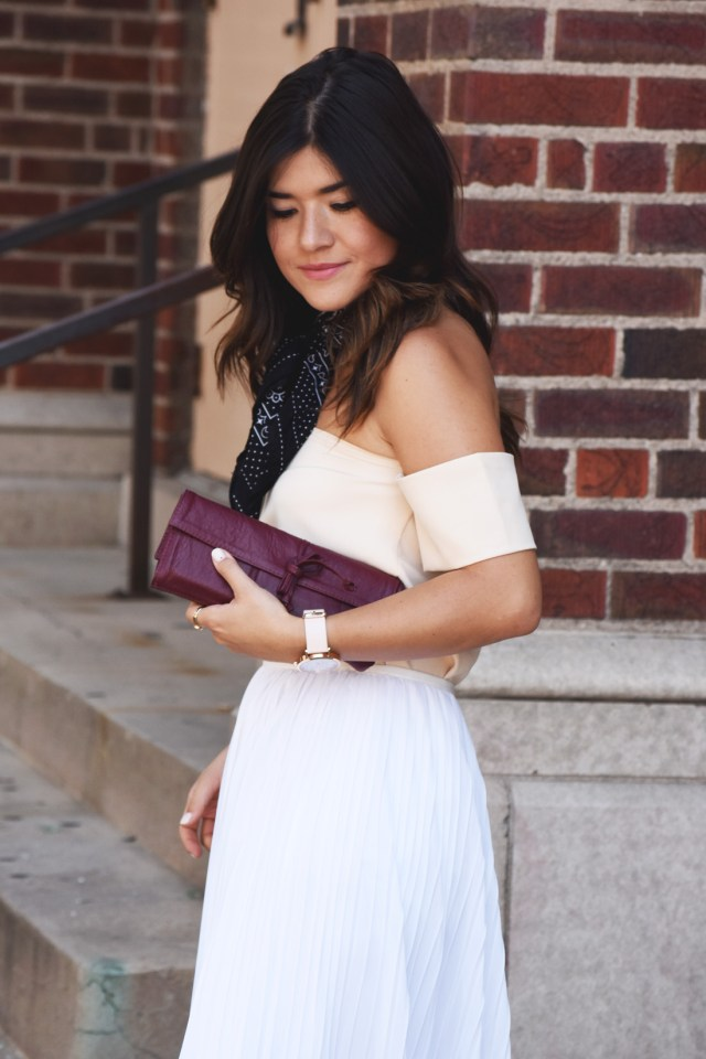 Carolina Hellal of Chic Talk wearing a SheIn off the shoulder top, Kensie pleated skirt, and Prett fast burgundy clutch.