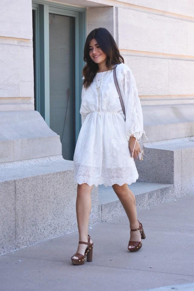 Carolina Hellal of Chic Talk wearing a white delicate VIPME dress, Kendra Scott gold accessories, and Wooden platforma via Macys.