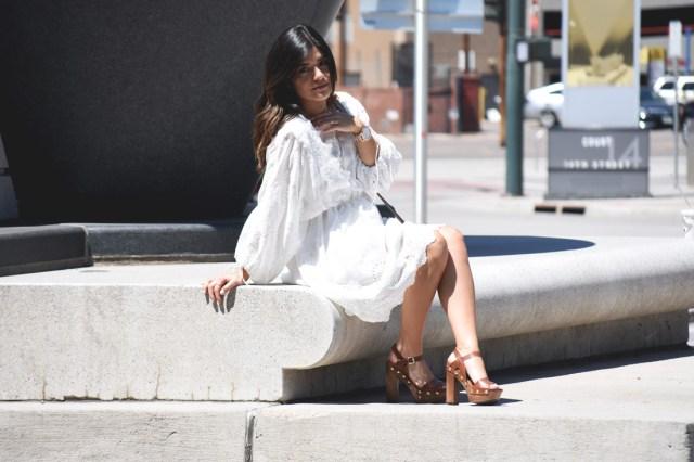 Carolina Hellal of Chic Talk wearing a white VIPME dress, wooden platforms via Macy's and Kendra Scott gold accessories.