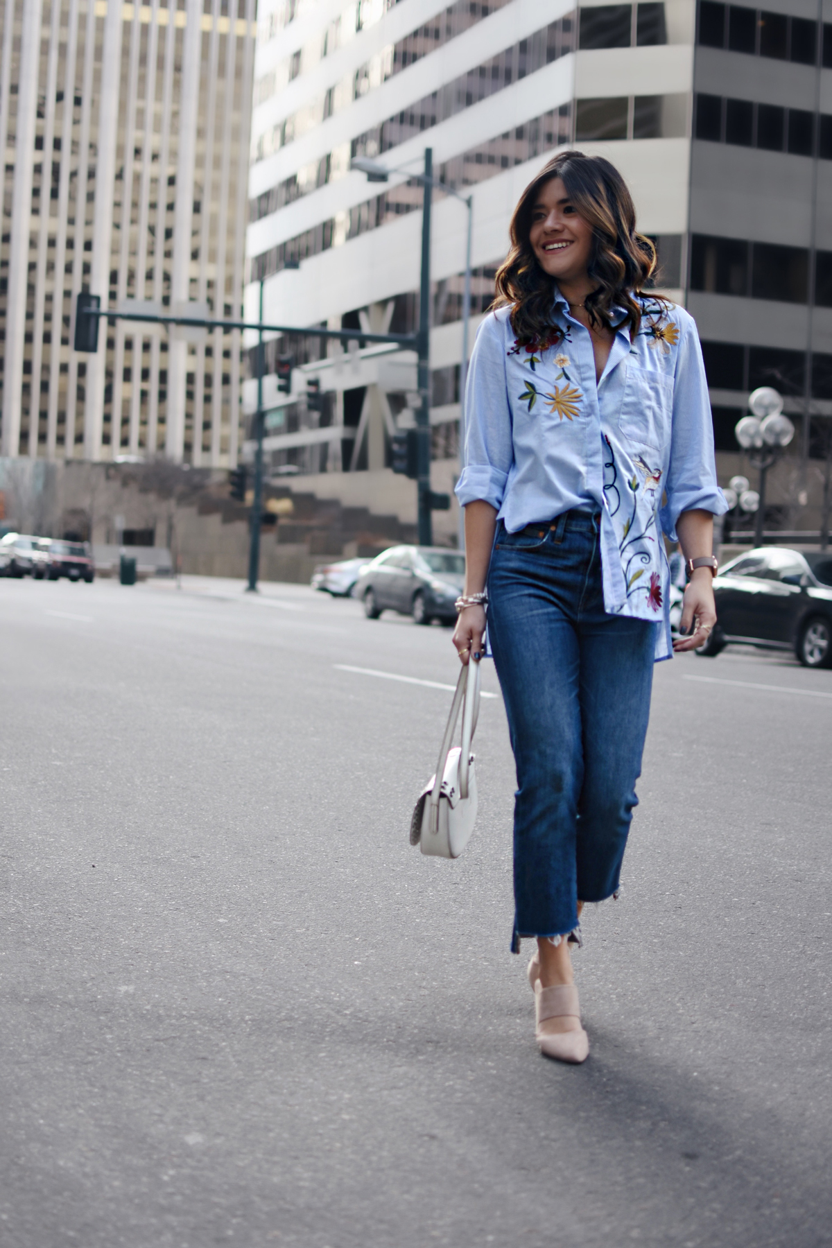 Carolina Hellal of Chic Talk wearing a Chicwish embroidered top, Madewell raw hem jeans, Frye white crossbody bag, and NA-KD fashion nude mules.