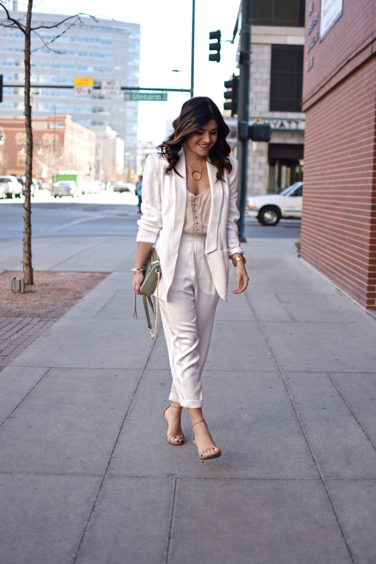 Carolina Hellal of CHIC TALK wearing a white suit via THACKER NYC, a Rebecca Minkoff bag, Steve Madden sandals, and NA-KD nude camisol