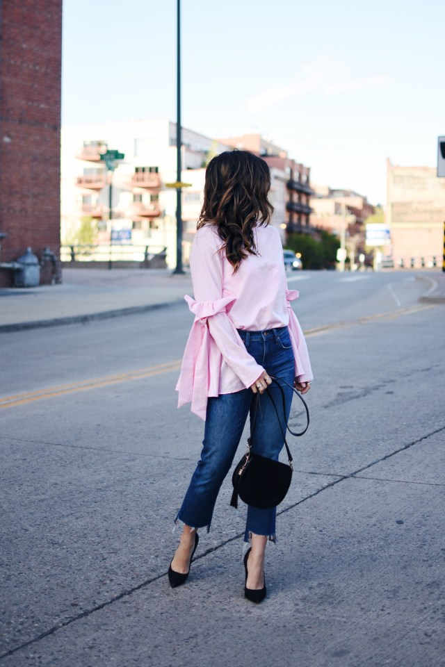 Carolina Hellal of Chic Talk wearing a Chicwish bell sleeve top, Madewell jeans, Steve Madden black pumps, Rebecca Minkoff black purse and Rayban Sunglasses