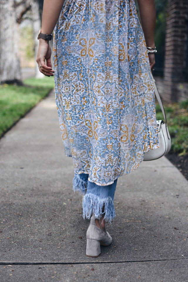 Carolina Hellal of Chic Talk wearing a floral chiffon tunic, fringe jeans, lace up pointy heels and a white crossbody bag