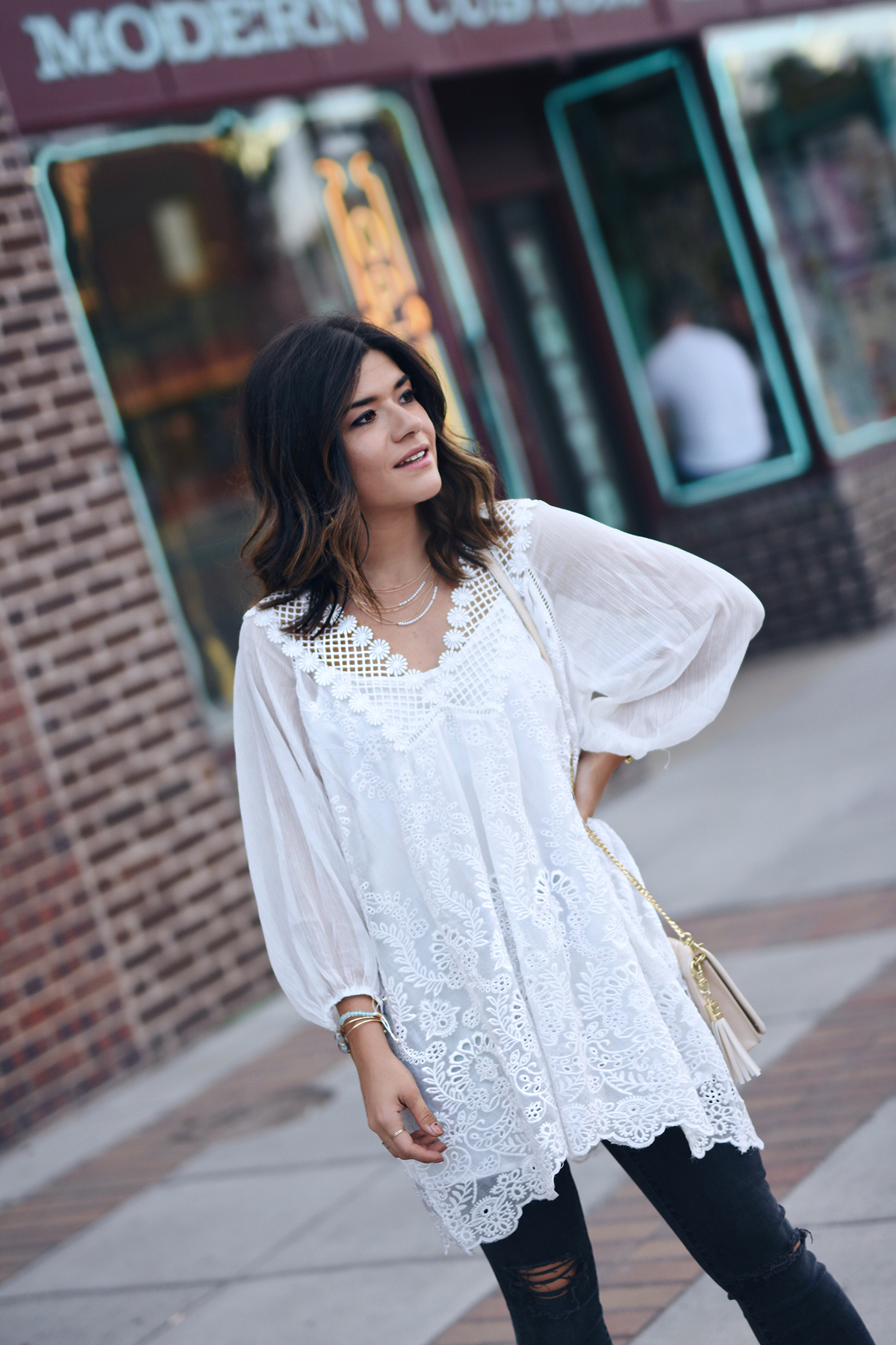 Carolina Hellal of Chic Talk wearing a Chicwish white tunic, Charming Charlie clutch, Madewell jeans and criss cross mules