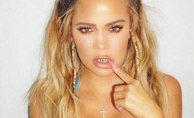 Pregnant Khloe Kardashian stuns in sexy crop top with teeth grill